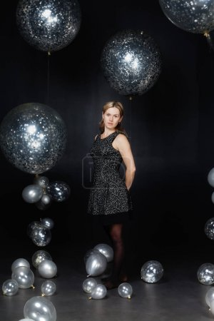 The woman is standing among silver balloons