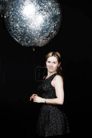The woman is standing with silver balloon
