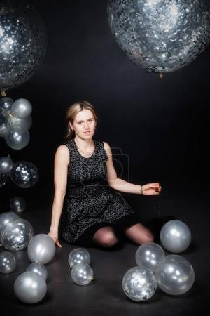 The woman is sitting among silver balloons