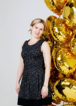 The woman is standing near gold balloons