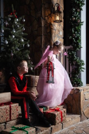 Boy and girl are sitting on the porch with gifts...