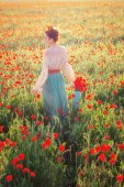 Girl in the field of poppies in the sunset light
