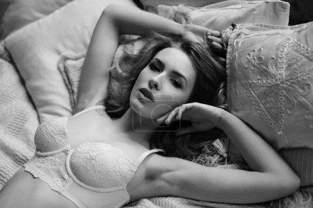 Photo pour Photo noir et blanc de magnifique jeune femme en lingerie posant sur le lit - image libre de droit