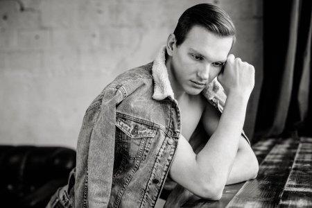 Photo pour Photo noir et blanc de jeune homme élégant posant dans une veste en denim déboutonnée - image libre de droit