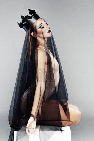 Photo pour Magnifique jeune femme avec du maquillage de mode posant en voile noir et couronne de papier - image libre de droit