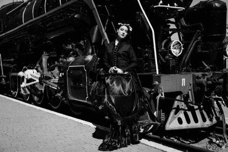 woman in vintage dress near steam locomotive