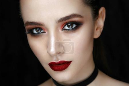 Close-up portrait of gorgeous young woman with fashion make-up against black background