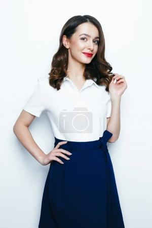 Pretty young brunette woman posing against white studio background