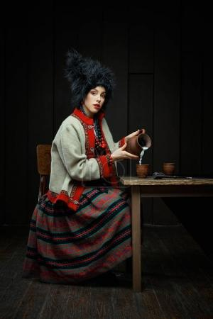 Gorgeouns young woman in ukrainian traditional costume holding clay jug of milk