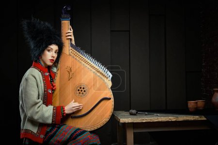 Photo for Gorgeouns young woman in ukrainian traditional costume with ukrainian musical instrument bandura - Royalty Free Image