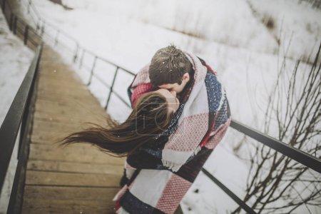 Photo pour Portrait d'amoureux du baiser enveloppé dans une couverture le jour de l'hiver - image libre de droit