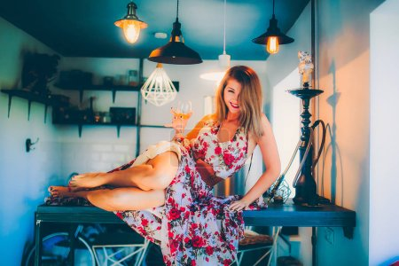 Photo pour Jeune belle femme assise dans la chambre intérieure avec un verre de vin à la main - image libre de droit