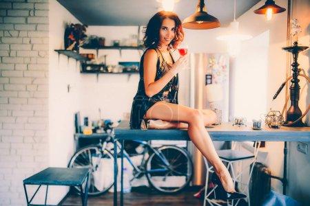 Photo pour Jeune belle femme sexy assise sur une table de cuisine avec un verre de vin à la main - image libre de droit