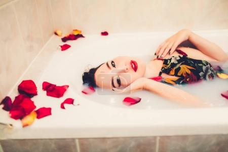 woman in wet dress with petals