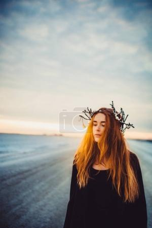 Beautiful red hair woman in black clothes with floral wreath on winter frozen lake outdoor