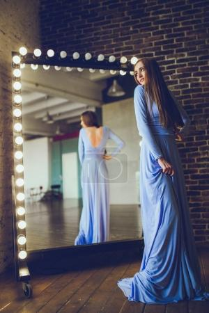 close-up of fashion woman in long purple dress near mirror on room background