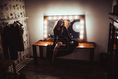 retrato de joven hermosa mujer de pelo rojo en vestido negro cerca del espejo con bombillas