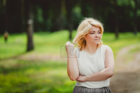portrait of elegant blonde middle aged woman in blurred park background