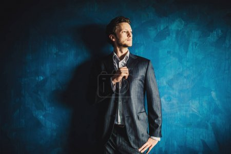 Photo for Portrait of young handsome businessman in suit on blue wall background - Royalty Free Image