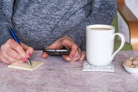 Photo pour Mains féminines tenant un téléphone portable et prenant des notes dans un bloc-notes, une tasse de boisson chaude sur une table, gros plan avec mise au point sélective - image libre de droit