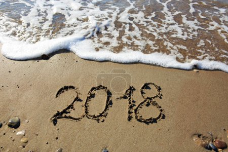 New year 2018 written in sand.