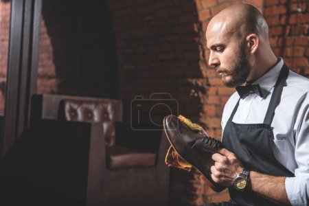 careful worker cleaning leather shoes