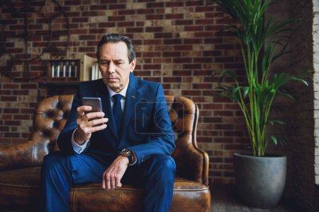 Photo pour Homme ayant subi une maturation concentré est assis sur le canapé. Il enfant à l'aide de son appareil à l'intérieur - image libre de droit