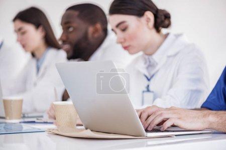 Los médicos serios que escriben el resumen en el portátil en el apartamento del hospital