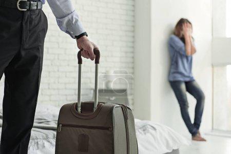 Photo pour Je t'abandonne. Une femme affligée se couvre le visage des mains. Focus sur l'homme gardant sa valise - image libre de droit