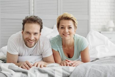Cheerful married man and woman relaxing on bedding
