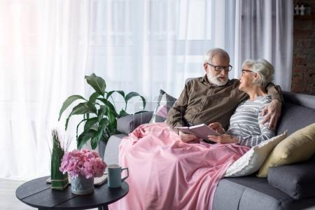 Amorous old man and woman resting at living room