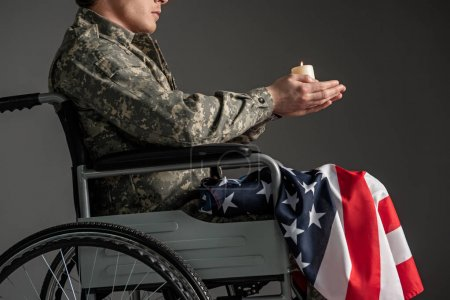 Photo for Disabled male soldier sitting in wheelchair. He is having candle in hands and usa flag on his knees. Isolated on grey background - Royalty Free Image