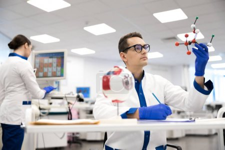 Photo for Laboratory worker studying molecule model and making notes stock photo - Royalty Free Image