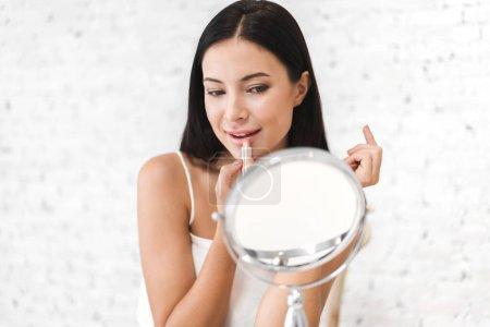 Photo pour Belle femme de sourire peau saine fraîche regardant sur le miroir et appréciant appliquant des lèvres avec la beauté rouge à la beauté de home.facial et au concept cosmétique - image libre de droit