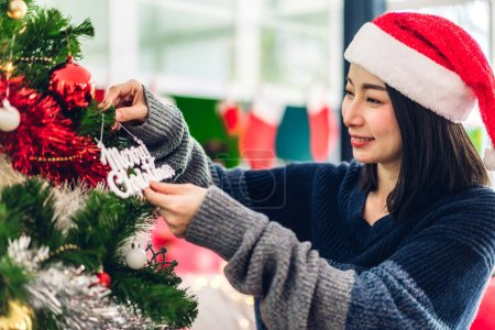 Photo for Asia woman in santa hats having fun decorating christmas tree and smiling while celebrating new year eve and enjoying spending time together in christmas time at home - Royalty Free Image