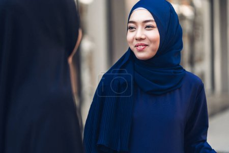 Portrait of happy arabic two friend muslim woman with hijab dress smiling and talking together at store