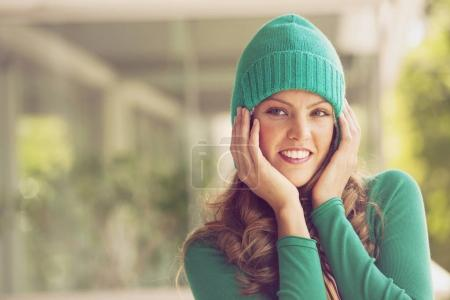 woman in green hat smiling