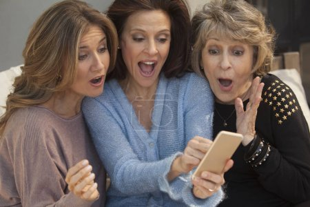 Three adult and senior women taking selfie  with mobile phone