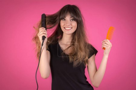 Woman with a hair curler and a comb. Girl with dis...