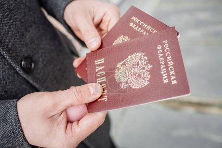 Photo pour Deux passeports russes à la main. Document officiel russe sur fond en plein air - image libre de droit