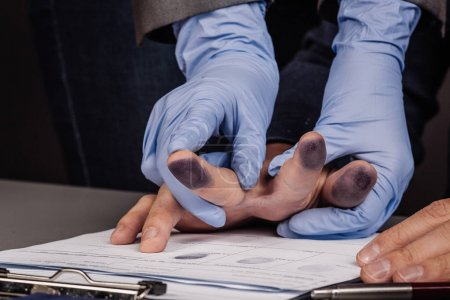 police takes fingerprints of a criminal