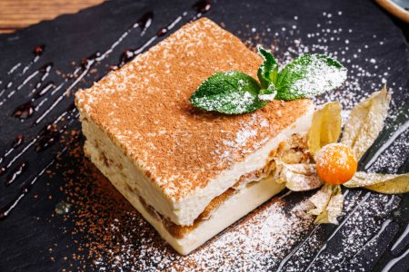Photo for Tiramisu cake with mint on plate closeup - Royalty Free Image