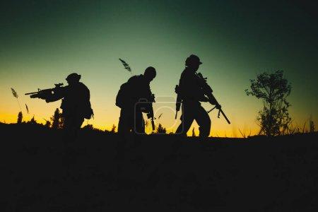 Photo pour Silhouette de soldats militaires armés la nuit. coup de feu, arme à feu, ciel coloré. concept militaire . - image libre de droit