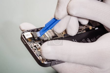 Close up hands of a service worker repairing modern smarphone.
