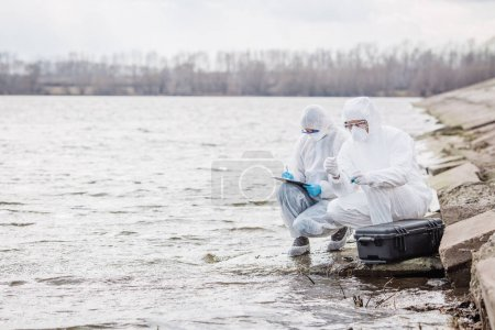 Scientists or biologists wearing protective uniforms working tog