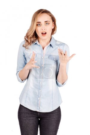 Young woman  in a jeans shirt having perplexed and puzzled expression on her face, isolated on white background. Negative human emotions, feelings, reaction