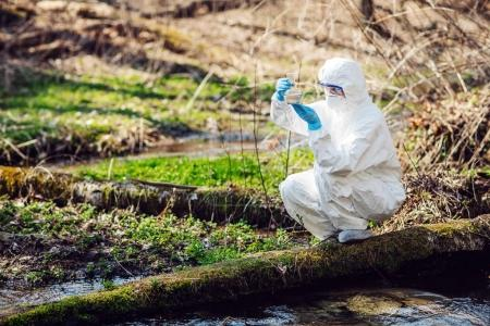 Closeup of a female scientist examining the liquid contents of flask in the forest. Ecology and environmental pollution concept.