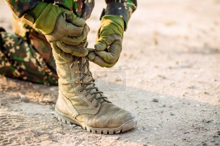 Photo for Rangers boots and hands tying bootlaces in desert - Royalty Free Image