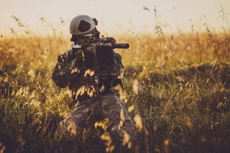 portrait of young soldier face with camouflage against a sunset