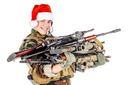 soldier with rifle wearing Santa claus cup and holding cardbox isolated on white background